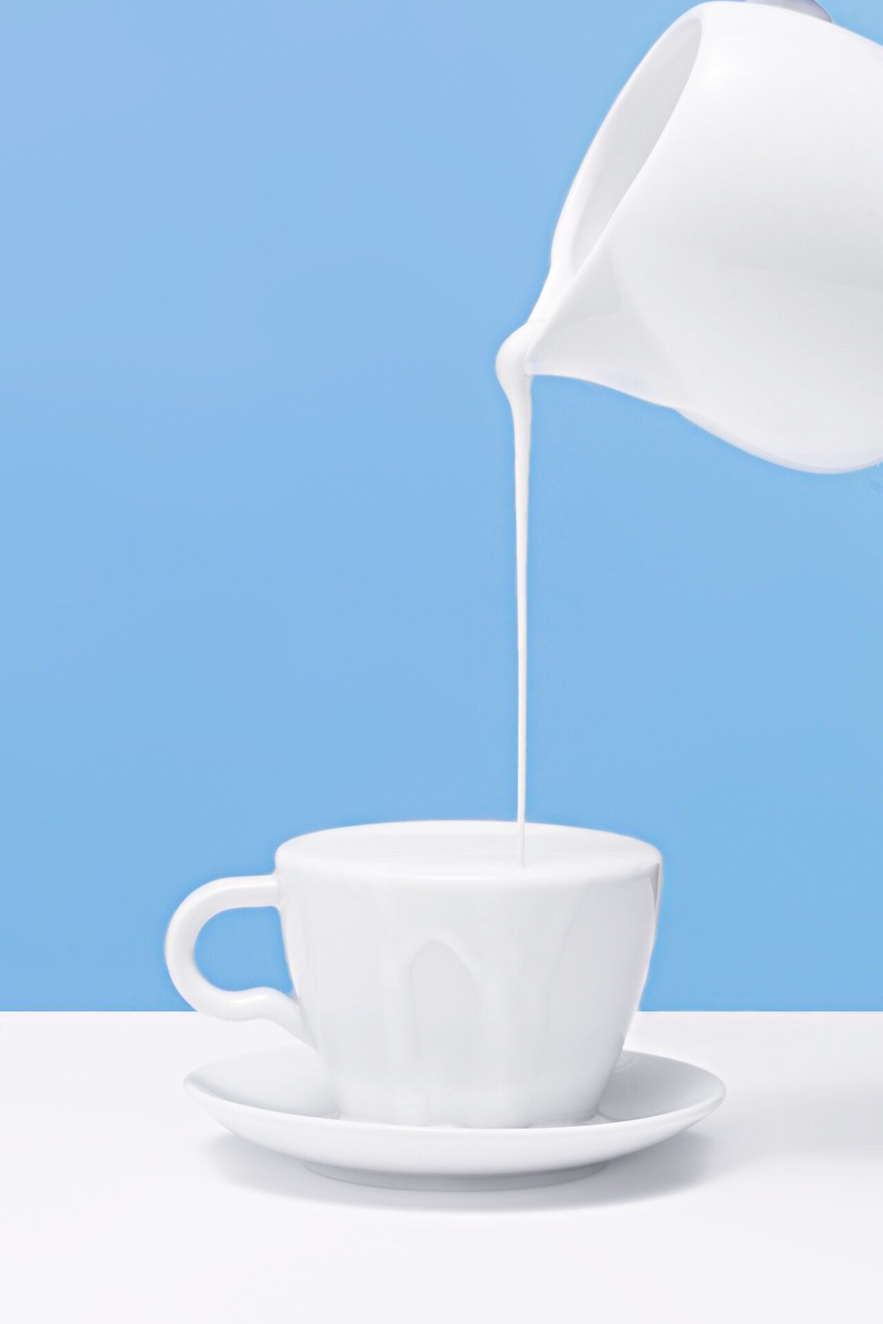 Close-up of jug pouring milk into coffee cup on table