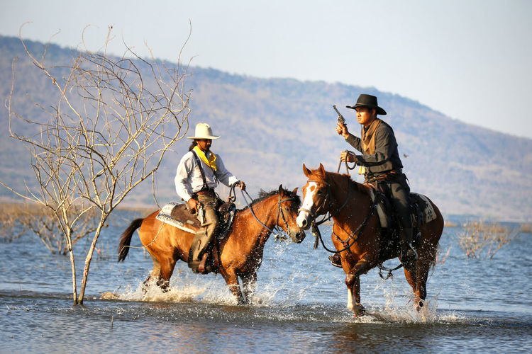 Mammal Domestic Animals Water Animal Wildlife Domestic Full Length Nature Livestock Ride Activity Riding Group Of Animals Horse Two People Men Hat Horseback Riding Day Cowboy Cowboy Hat Outdoors Mature Men