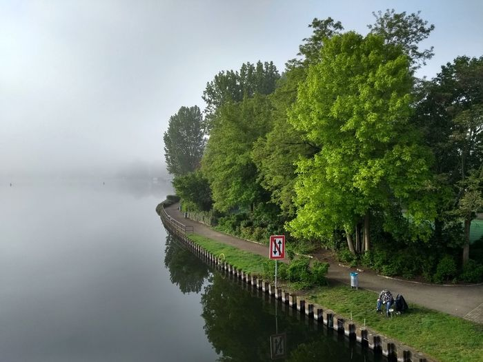 Sky Overcast Tree Getting Away From It All Reflection River Spring Springtime Water Waterfront Beauty In Nature Nature Fishing Tree Water Women Men Lake Sky Foggy Fog Mist Weather Tranquil Scene Tranquility Calm Lush - Description Growing
