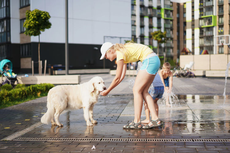 Side view of young woman playing with dog on street