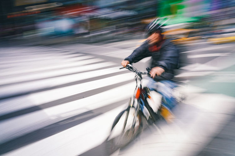 Blurred motion of man riding bicycle on road