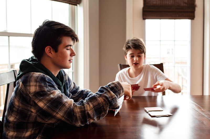 Portrait of siblings sitting on table
