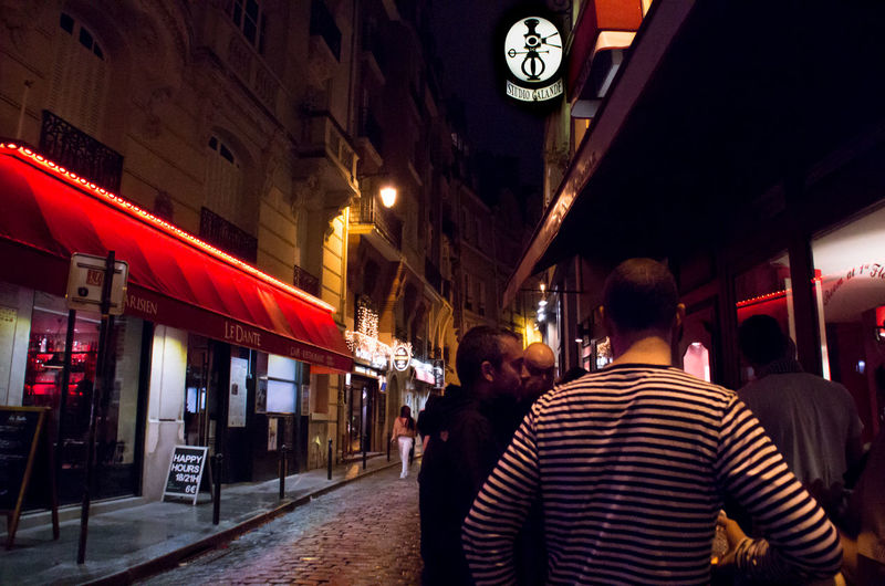Architecture Awning Building Exterior Built Structure Casual Clothing City City Life Cobblestone France Group Of People Illuminated Lights Men Night Paris Person Street Stripes Pattern Studio Galande People And Places