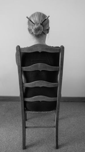 Man sitting on chair against wall