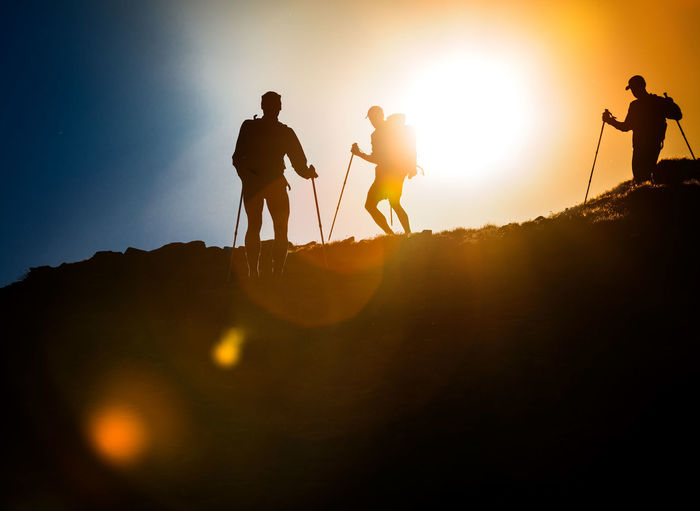 Silhouette men on mountain against sky during sunset