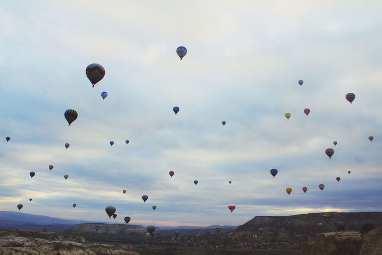 Hot air balloons over landscape against cloudy sky