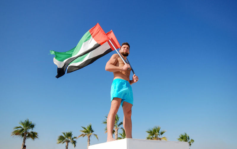 Low angle view of mid adult man holding flags while standing against clear blue sky