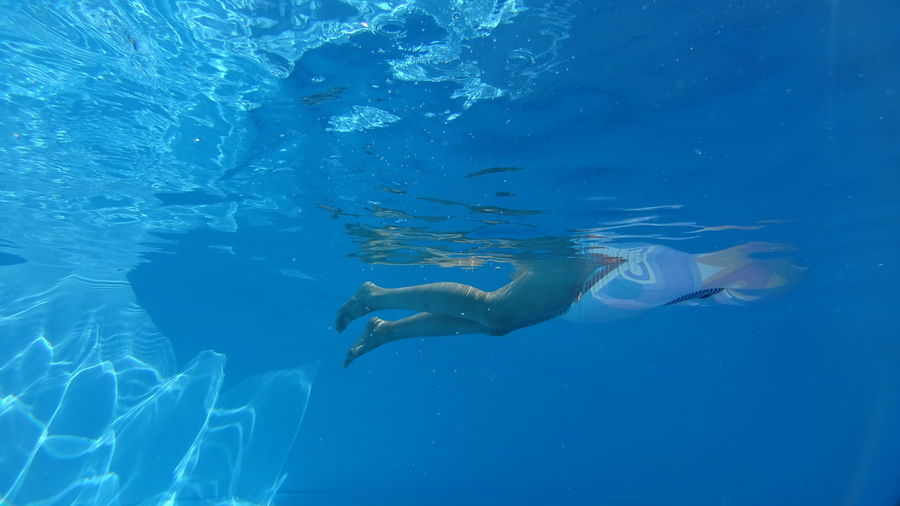 Low section of woman swimming in blue sea