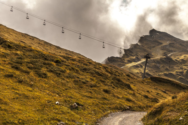 Side view of  chairlift againstcloudy  sky