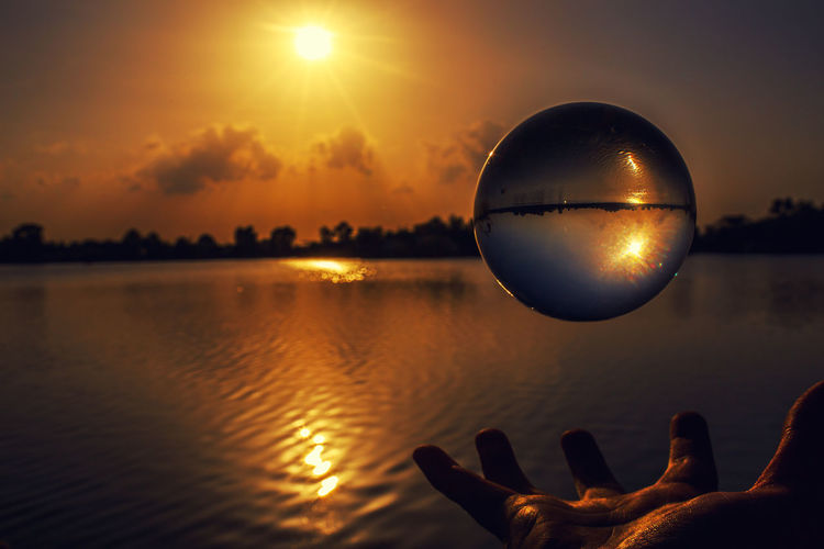Cropped Hand Levitating Crystal Ball By Lake During Sunset