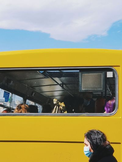 Rear view of people on yellow glass against sky