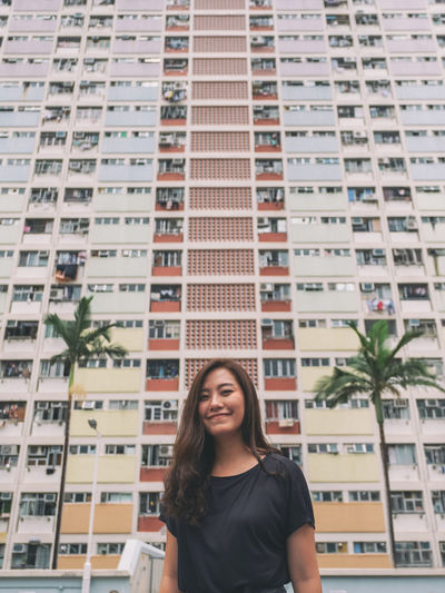 Portrait of smiling young woman standing against buildings