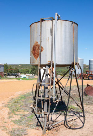 Elevated fuel storage tank on stand in rural Western Australia farmland. Agriculture Container Cylinder Day Elevated Equipment Farmland Fuel Gas Hosing Ladder Metallic Nozzle Outdoors Petrol Pump Rural Rusted Sand Silver  Sky Sprayer Stank Storage Tank