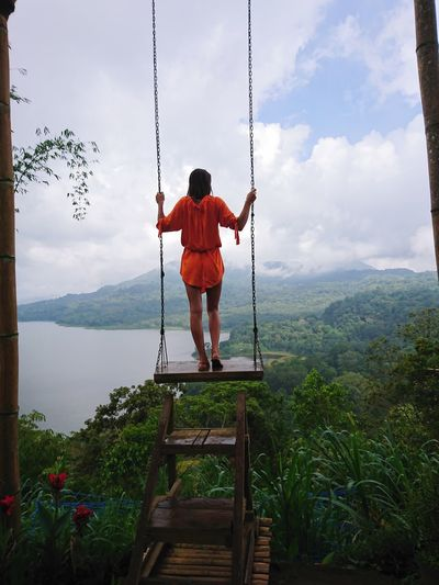 Rear view of woman standing on swing against forest
