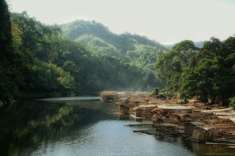 Bamboo shacks by river during foggy weather
