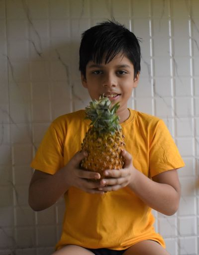 Portrait of smiling boy holding pineapple against wall