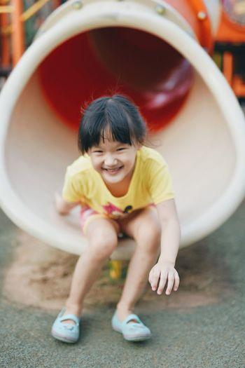 Full length portrait of smiling girl sitting in slide