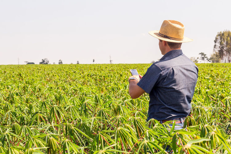Man standing in farm against sky
