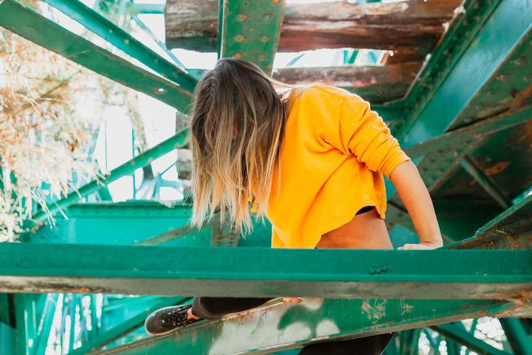 Young woman sitting on railway bridge