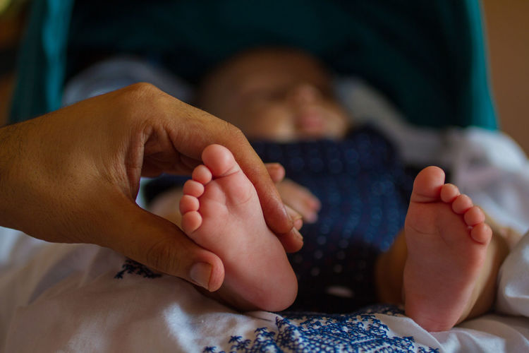 Cropped Mother Hand Holding Baby Leg On Bed At Home