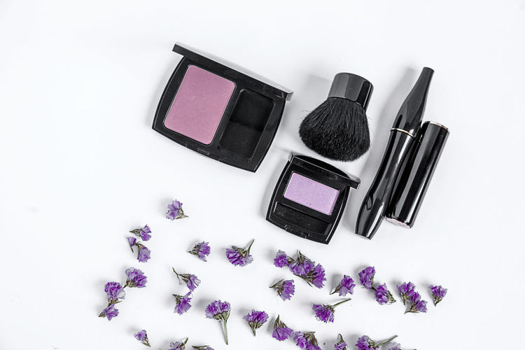 Directly above shot of make-up products with flowers on white background
