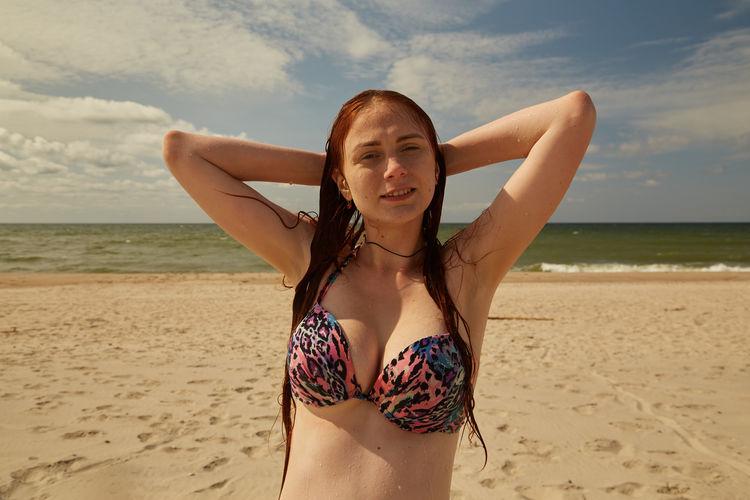 Portrait of young woman wearing bikini on beach against sky