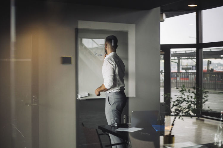 Full length of a man standing by window