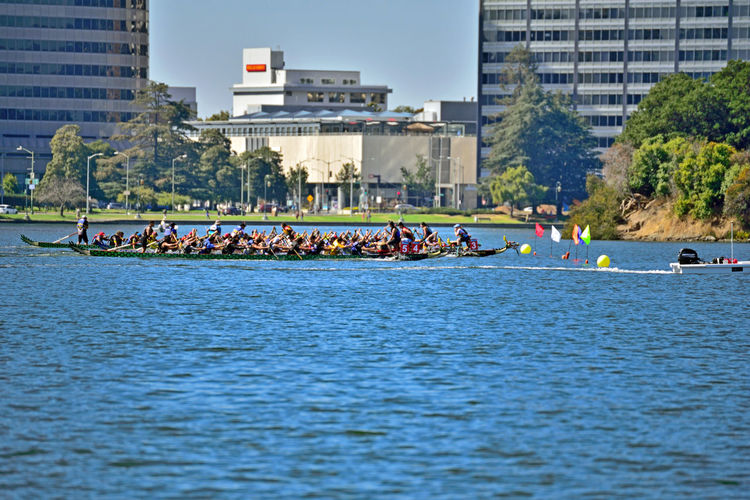 Dragon Boat Racing @ Lake Merritt 3 The Color Of Sport Lake Merritt Oakland, Ca. Rowing Rowing Boats Rowing Teams Sports Watersports Aquactic Sports RowingCompetition Dragon Boats Racing Flags Lane Markers Lake Urban Life Office Buildings Trees Water City Life Weekend Activities Enjoying Life Outdoors Urban Landscape