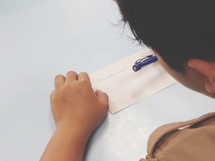 Close-up of man writing on envelope