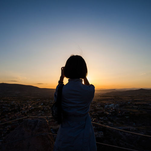 Rear view of woman standing at observation point against clear sky at sunset