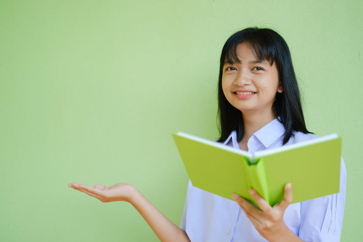 Portrait of a smiling young woman holding book