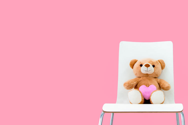 Full length of stuffed toy against pink background
