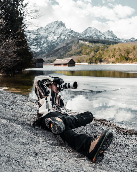 Full length of man photographing while lying down by lake against sky