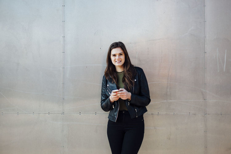 Portrait of smiling young woman standing against metallic wall