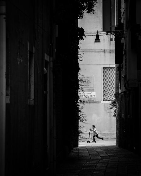 Silhouette person walking on street amidst buildings
