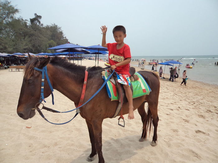 Full length of boy riding horse at beach