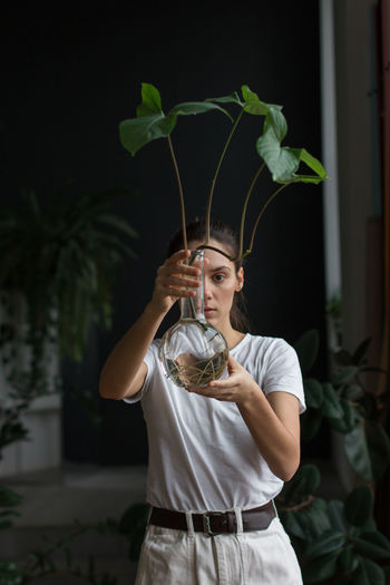 Portrait of a young woman holding plant