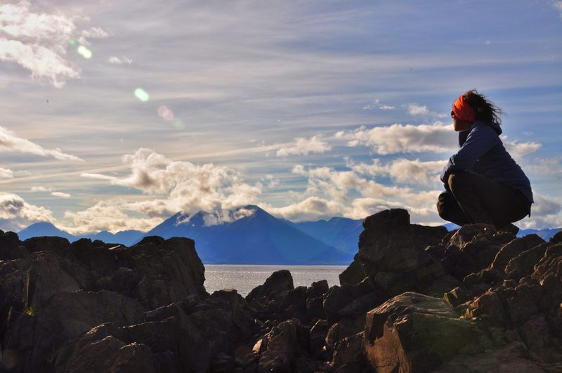Woman crouching on rock against sky