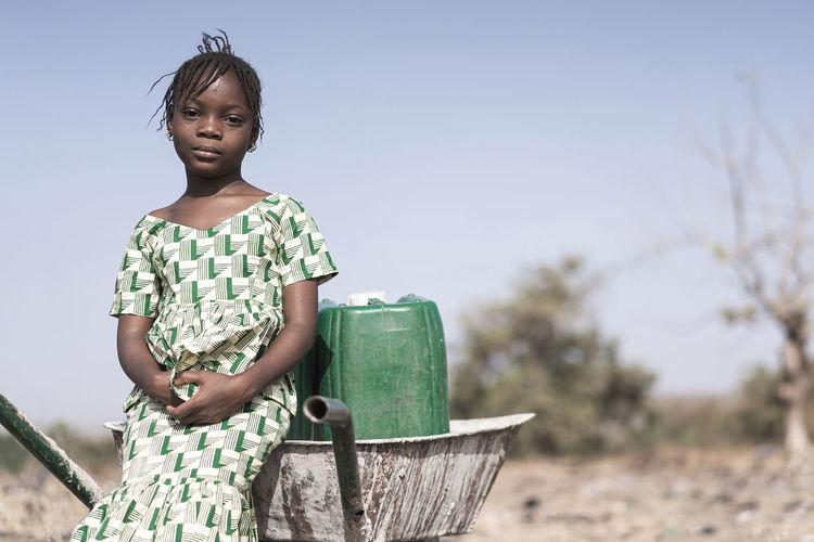 Portrait of girl sitting on wheelbarrow at land