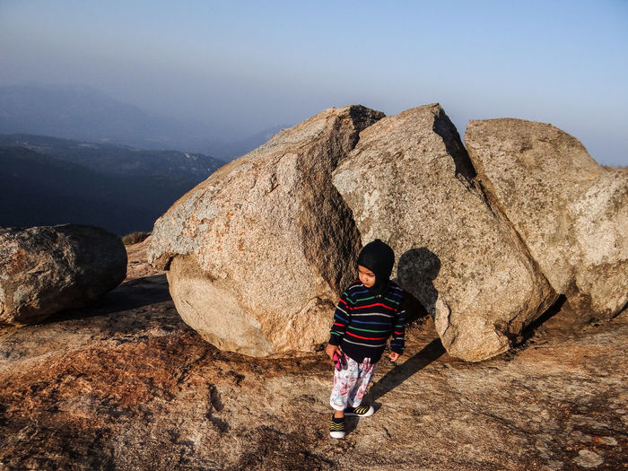 Boy standing on mountain against sky