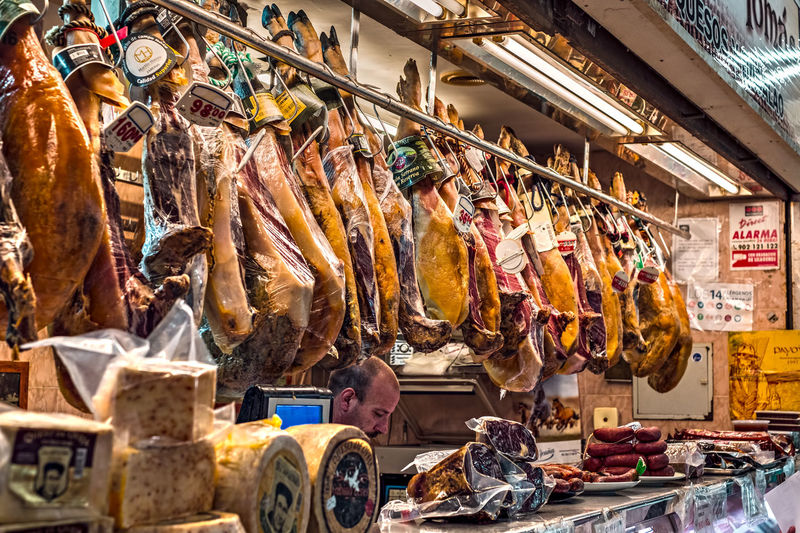 Malaga, Spain - August 09, 2018. Spanish prosciutto or jamon iberico and other Spanish specialities at the market of Ataranzanas Central Market, Malaga, Spain Ataranzanas Jamon Jamon Bellota Malaga SPAIN Spanish Spanish Food Specialities  Abundance Arrangement Business Buying Choice Consumerism Food Food And Drink For Sale Freshness Jamon Serrano Jamón Ibérico Large Group Of Objects Market Market Stall People Prosciutto Prosciutto Crudo Prosciutto Melone Real People Retail  Retail Display Sale Shopping Small Business Spanish Culture Store Variation Women