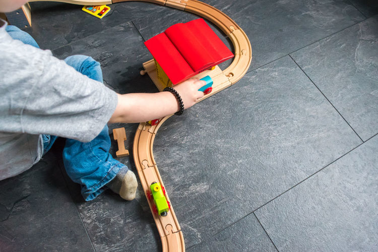 Cropped image of boy playing with train set on floor at home