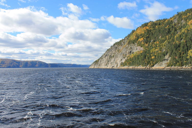 Scenic view of saguenay river and mountains against blue sky