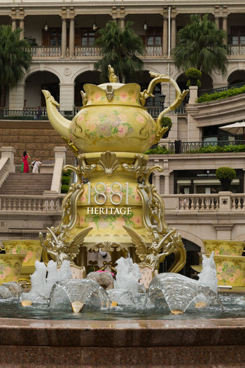 Angel Bollards Day Fountain Gold Gold Colored Gold Teapot Outdoors Palaces Palm Tree Sculpture Statue Steps And Staircases Tea Cup Teapot Tree Water Woman In Red