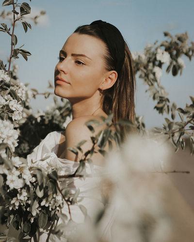 Portrait of young woman against plants