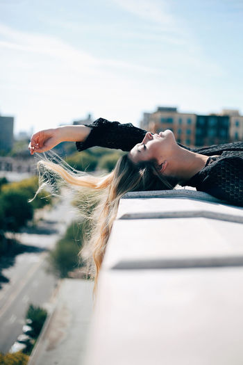 Side view of young woman lying on retaining wall against sky