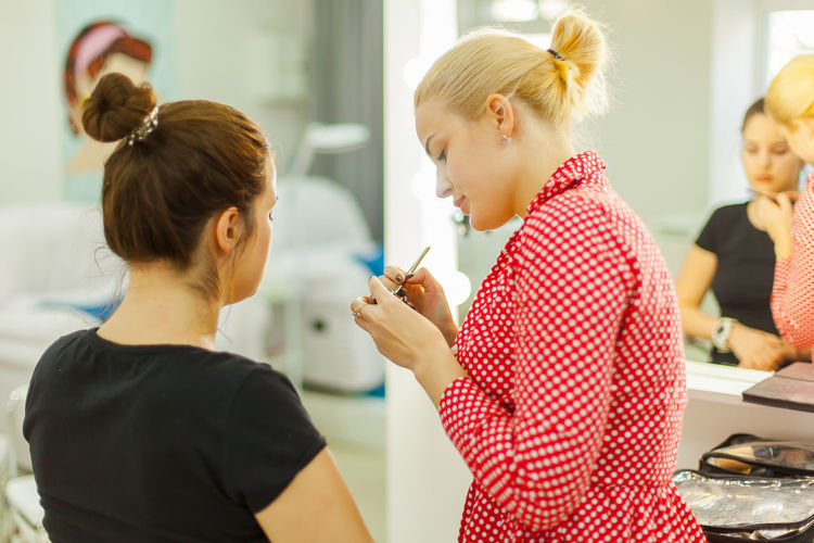 Side View Of Woman Applying Make-Up Of Customer Face