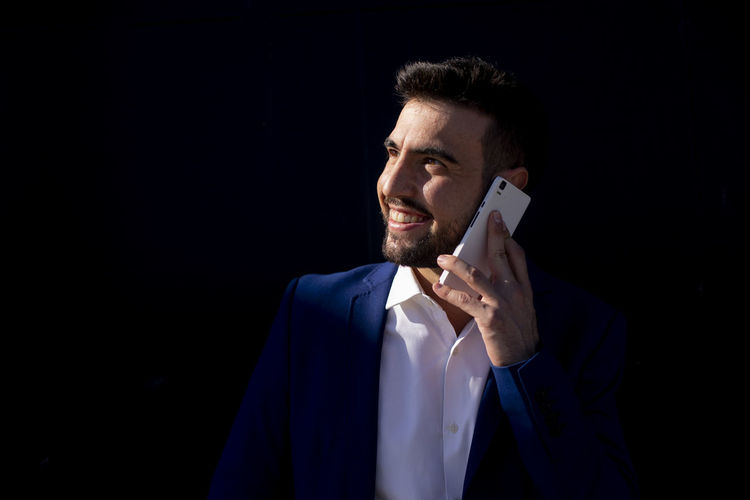 Mid adult man using mobile phone against black background