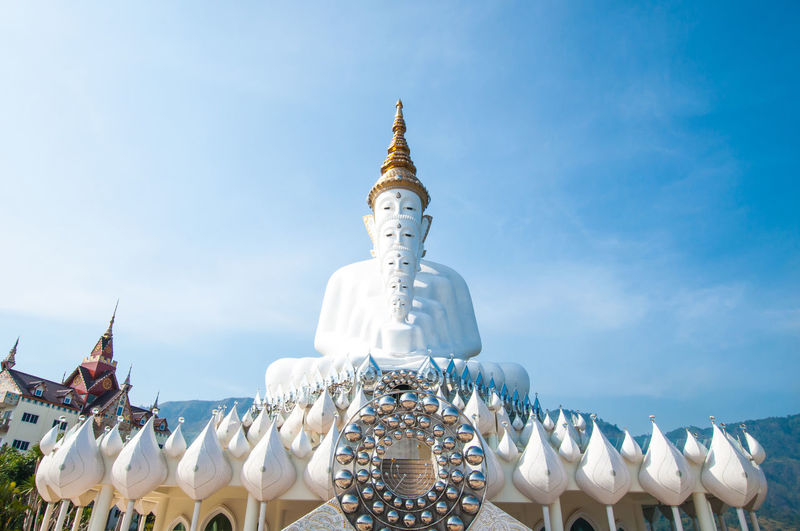 Low angle view of white buddha statues at wat pha son kaew against sky