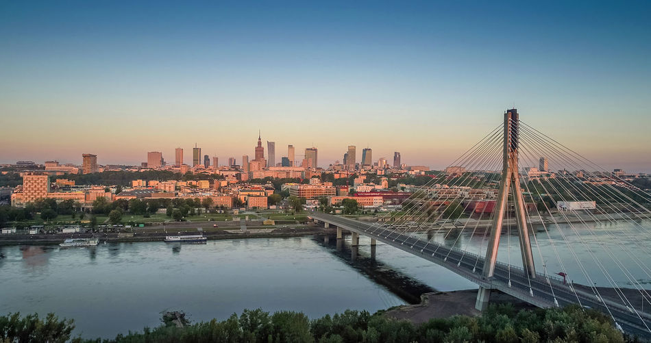 Aerial panorama of Warsaw, Poland at sunrise including Swietokrzyski Bridge over the Vistual river and City center in a distance Architecture Bridge - Man Made Structure Building Exterior Built Structure City Cityscape Clear Sky Connection Day Flying High Modern No People Outdoors River Sky Skyscraper Transportation Travel Destinations Urban Skyline Water